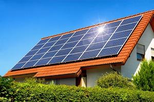 Solaranlage auf einem Hausdach unter dem strahlend blauen Himmel, mit der Reflektion der Sonne
